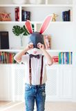 Upset young bunny rabbit character crying alone at home stock photo