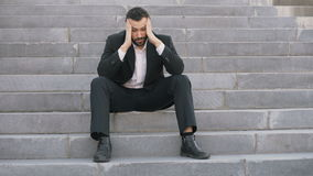Upset young business man having stress and sitting on stairs in street. Businessman having deal problems concept. Upset young business man having stress and stock video