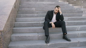 Upset young business man having stress and sitting on stairs in street. Businessman having deal problems concept. Upset young business man having stress and stock footage