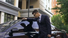 Upset young businessman standing near luxurious car, talking on phone, bad news stock video