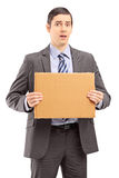 Upset young businessman in suit holding a piece of cardboard royalty free stock image