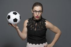 Upset young businesswoman - football fan holding black and white soccer ball in hands stock image