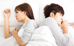 Upset young couple  lying side by side Royalty Free Stock Photos
