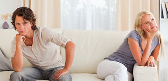 Upset young couple sitting on a couch Royalty Free Stock Images