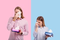 Upset young couple wiping tears with tissues. Bitter tears. Sad young couple crying and wiping tears with tissues while posing against blue and pink backgrounds Stock Photography