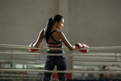 Upset young fighter boxer girl wearing boxing gloves in gym. royalty free stock photos