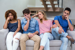 Upset young friends sitting on sofa Stock Image