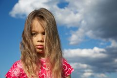 Upset Young Girl against Cloudy Sky Stock Images