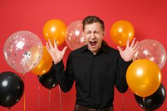 Upset young man in black classic shirt spreading hands, screaming on bright red background air balloons. St. Valentine`s stock image