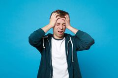 Upset young man in casual clothes screaming crying putting hands on head keeping eyes closed isolated on blue wall royalty free stock photography