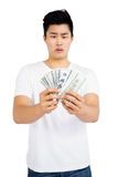 Upset young man counting fanned out currency notes Royalty Free Stock Image