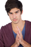 Upset young man with hands together Stock Image