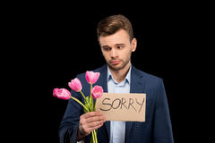 Upset young man holding pink tulips bouquet and sorry sign Stock Images