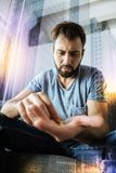 Upset young man looking at his pills and feeling unwell. Pills again. Young calm upset man sitting alone and feeling awful while being in his room and putting Stock Image