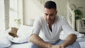 Upset young man sitting in bed suffer of problems while his girlfriend sleep in bedroom. Upset young men sitting in bed suffer of problems while his girlfriend royalty free stock image