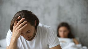 Man upset after quarrel sitting on bed, woman at background. Upset young man sitting on the side of bed not talking to woman at background after quarrel, serious stock footage
