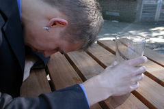 An upset young man in a suit finishes his beer. A dissapointed buisnessman drinks in a back alley beer garden. His glass is empty Royalty Free Stock Images