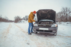 Upset young men look under the hood and call service Royalty Free Stock Images