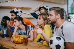 upset young multicultural friends in soccer ball hats with hand clappers and fan horn watching football match stock photos