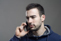 Upset young stubble man listening on the cellphone Royalty Free Stock Images