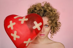 Upset young woman with ball in shape of heart Royalty Free Stock Images
