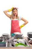 Upset young woman behind a sink filled with dirty plates stock photography