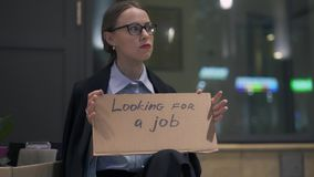 Upset woman sitting with cardboard looking for a job sign in night street