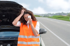 Upset young woman crying after a car breakdown Royalty Free Stock Image