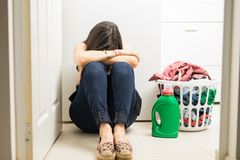 Upset woman in laundry room sitting with laundry basket and dete. Upset young woman feeling frustrated sitting on laundry room floor Royalty Free Stock Photos