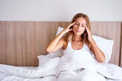 Upset young woman. Headache. Upset young woman touching her head while sitting on bed at home Royalty Free Stock Image