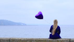 Upset young woman holding violet heart balloon. stock footage