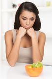 Upset young woman keeping diet and eating vegetables. Royalty Free Stock Photos