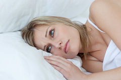 Upset young woman lying on her bed Stock Photography