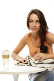Upset young woman with newspaper and latte macchia. To at a table on white background royalty free stock image