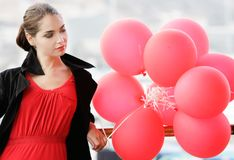 Upset young woman with red balloons Stock Photo
