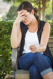 Upset Young Woman Sitting Alone on Bench Stock Photography
