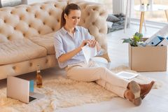 Upset young woman tearing paper while sitting on the floor stock image