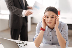 Upset young woman wrinkling her forehead. Want to change my job. Exhausted girl sitting at her workplace leaning her head on the hands pressing lips while Royalty Free Stock Photo