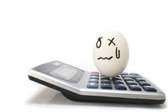 Upsetting egg on the electronic calculator Stock Photos