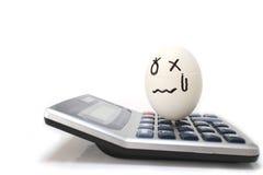 Upsetting egg on the electronic calculator Stock Photos