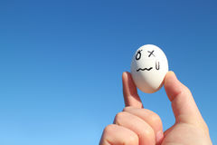 Upsetting egg and the hand in the blue sky Royalty Free Stock Images