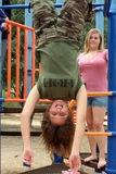 Upside Down. Teenage girl swinging upside down on the monkey bars in the park Royalty Free Stock Photo
