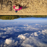 Upside Down. Young teenage white Caucasian female floating above a beautiful field landscape with upside down clouds Stock Images
