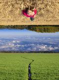 Upside Down. Attractive young teenage white Caucasian female floating above a beautiful field landscape with upside down clouds Stock Photo