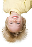 Upside down. Little boy is upside down on white background royalty free stock image