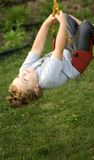 Upside Down. Young boy hanging upside down from playground swing royalty free stock images