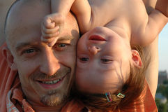 UpSide Down. Father and baby daughter playing on a summer evening at sunset Stock Images