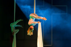 Upside Down Aerialists. Two aerialists in white hang upside down between tricks against blue stage lights and smoke with a giant cross in the background Royalty Free Stock Photos