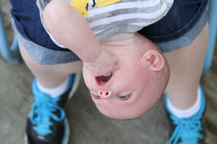 Upside down baby boy and mommy's feet closeup Royalty Free Stock Images