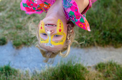 Upside down. Beautiful blond girl with yellow butterfly face-painting laughing royalty free stock photos
